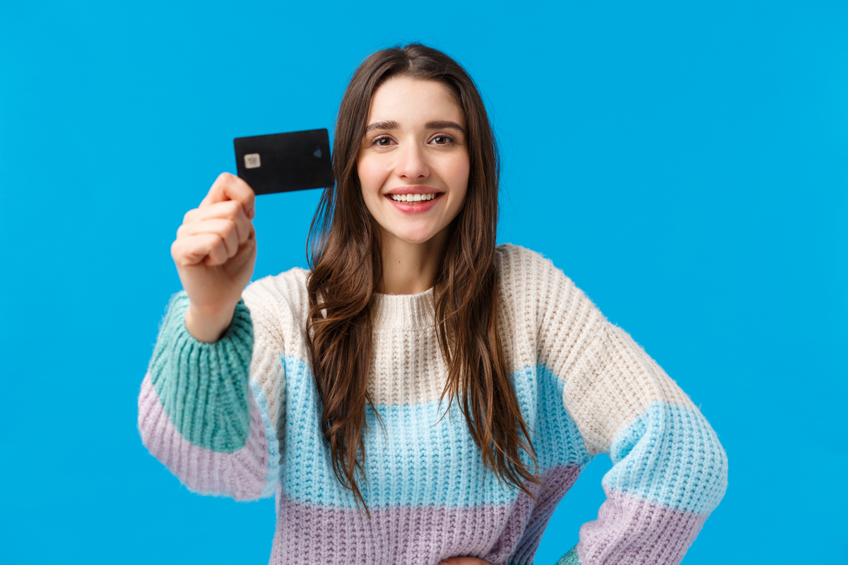 Woman holding up her favorite small business credit card.