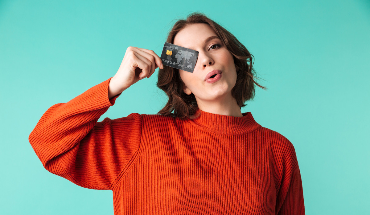 Woman holding a credit card over her eye.